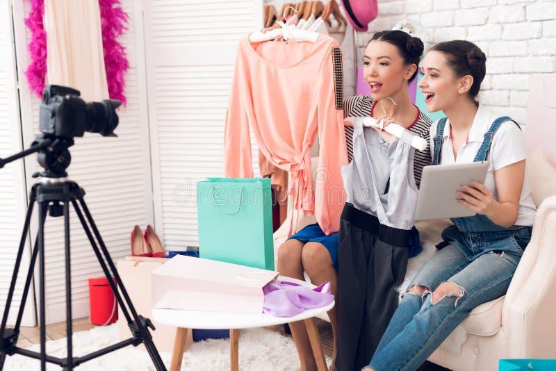 Deux filles de blogger de mode supportent les robes et le comprimé colorés à l'appareil-photo photo libre de droits