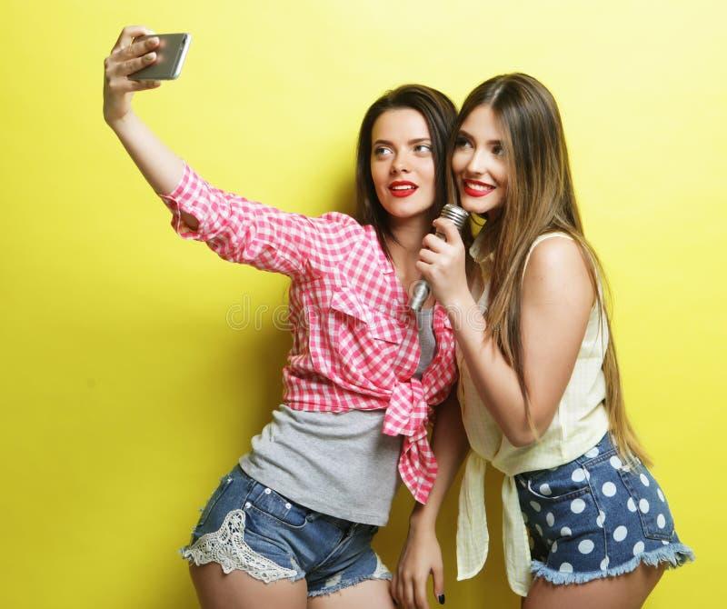 Deux filles de hippie de beauté avec un microphone prennent le selfi image libre de droits