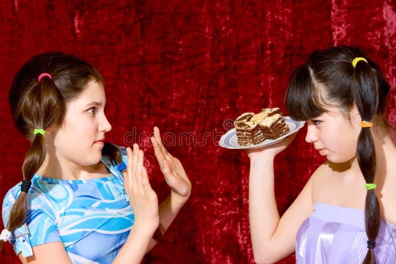 Deux filles de l'adolescence avec le gâteau images stock