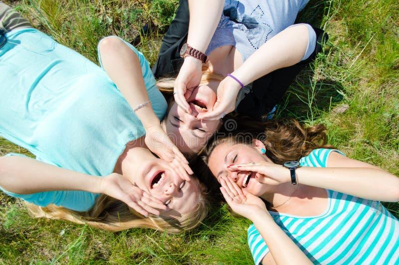 Deux filles de l'adolescence heureuses se trouvant sur l'herbe verte et tenant des mains image stock