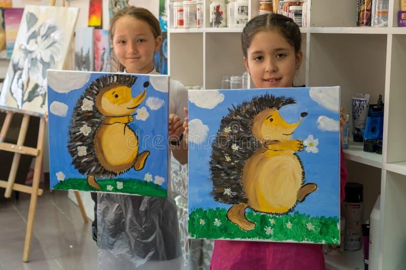 Deux filles de l'adolescence montrent leurs images Intérieur de l'école d'art pour les enfants de dessin Cr?ativit? et concept de photo stock