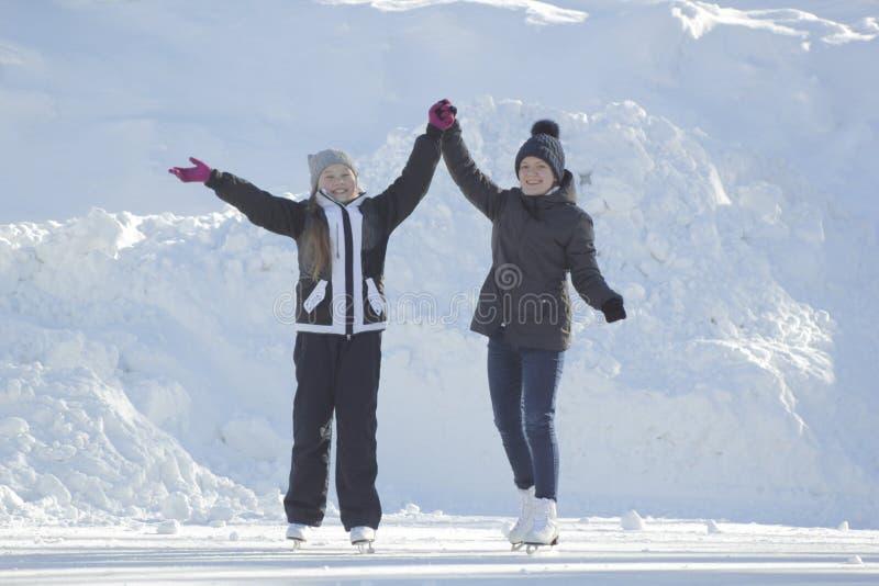 Deux filles de l'adolescence patinant sur la patinoire après école image libre de droits