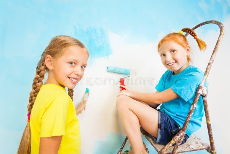 Deux filles de sourire avec le mur bleu sur un fond images libres de droits
