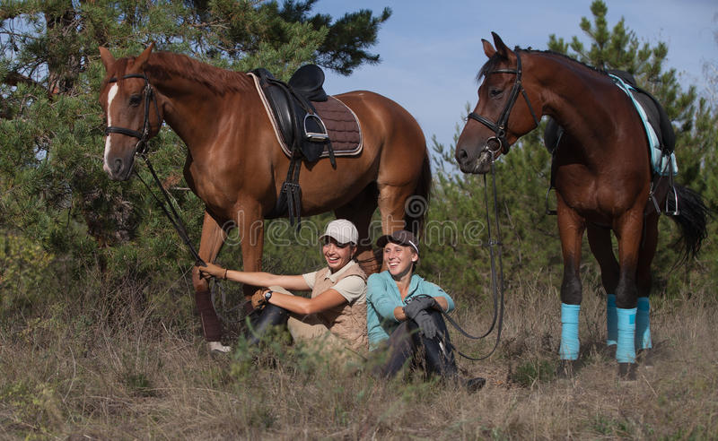 Deux filles de sourire avec leurs beaux chevaux image stock