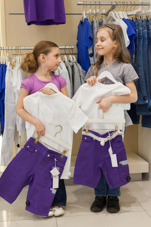 Deux filles de sourire essayant sur la même robe dans le magasin photographie stock libre de droits