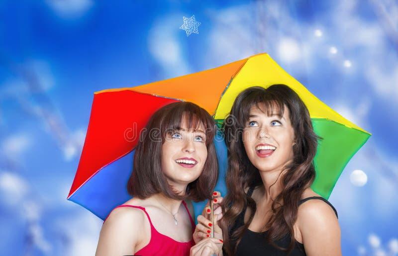 Deux filles de sourire regardant la chute de flocon de neige photo libre de droits
