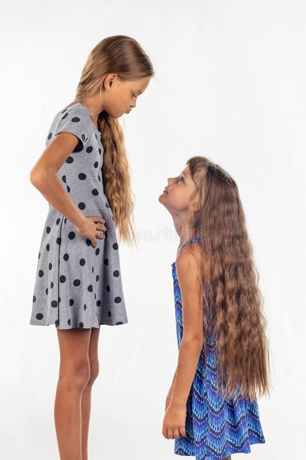Deux filles de stature différente, une se sont tenues sur une chaise et sont devenues encore plus grandes photo libre de droits