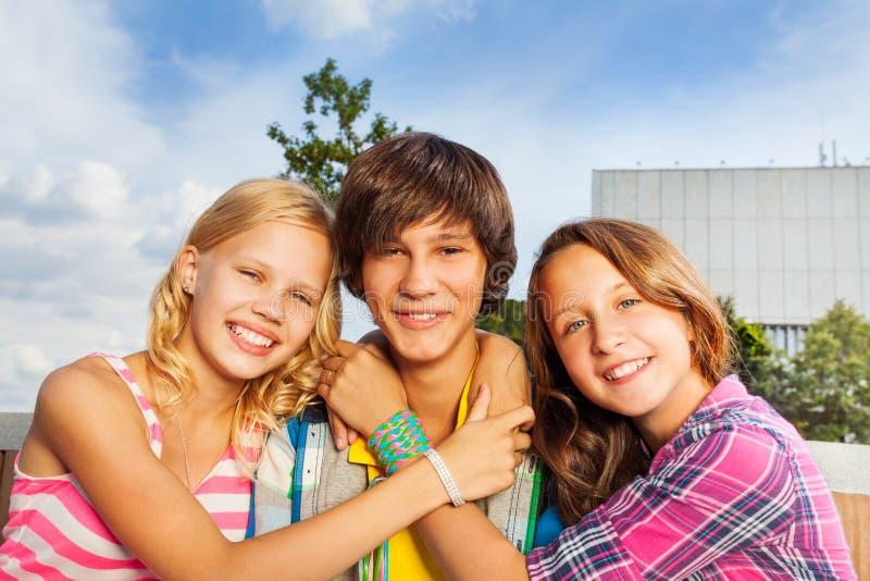 Deux filles embrassant le cou et le sourire du garçon heureusement photo stock