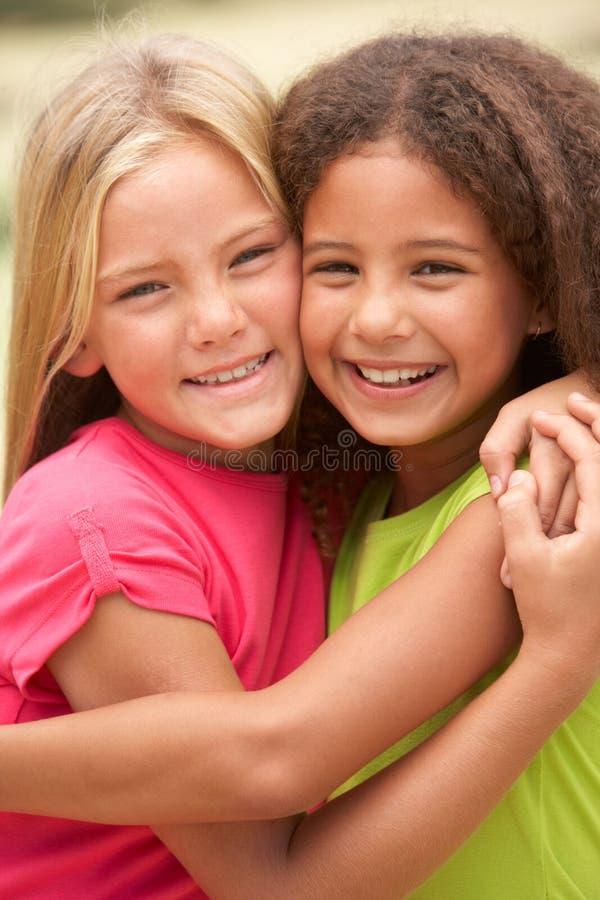 Deux filles en stationnement se donnant l'étreinte photographie stock