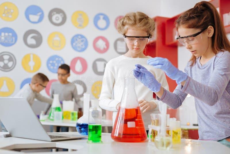 Deux filles entreprenant l'expérience chimique dans le laboratoire d'école photo libre de droits