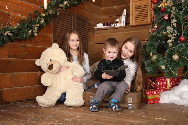 deux filles et un petit garçon s'asseyent sur le plancher contre un mur en bois photographie stock libre de droits