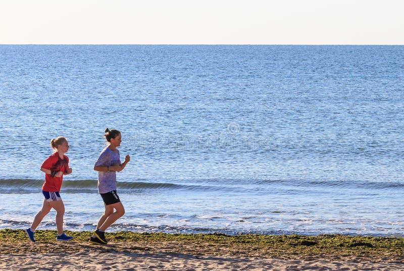 Deux filles exécutant sur la plage photos stock