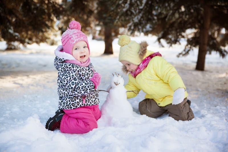 Deux filles font un bonhomme de neige photographie stock