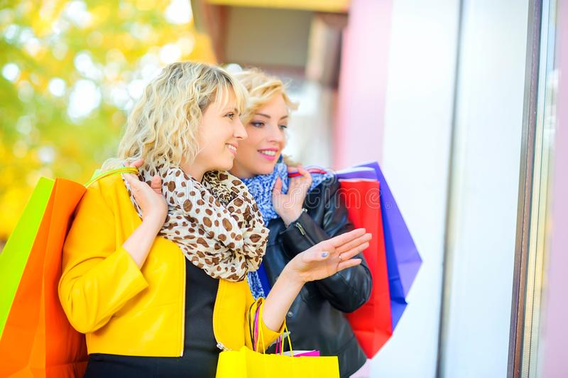 Deux filles heureuses avec des sacs ? provisions montrent la main et le regard ? la fen?tre de magasin photos libres de droits