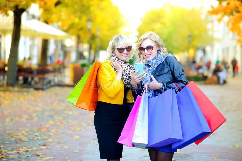 Deux filles heureuses dans des lunettes de soleil avec des sacs à provisions images stock