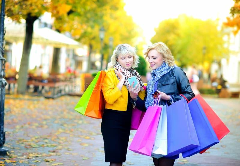 Deux filles heureuses dans des lunettes de soleil avec des sacs à provisions, emploient un smartphone et un sourire images stock