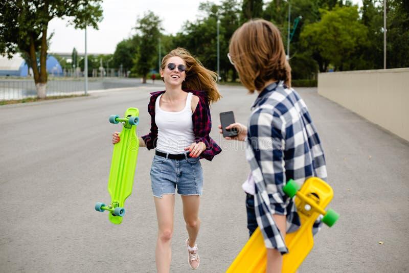 Deux filles heureuses gaies dans l'équipement de hippie ayant l'amusement à la rue pendant des vacances d'été images stock