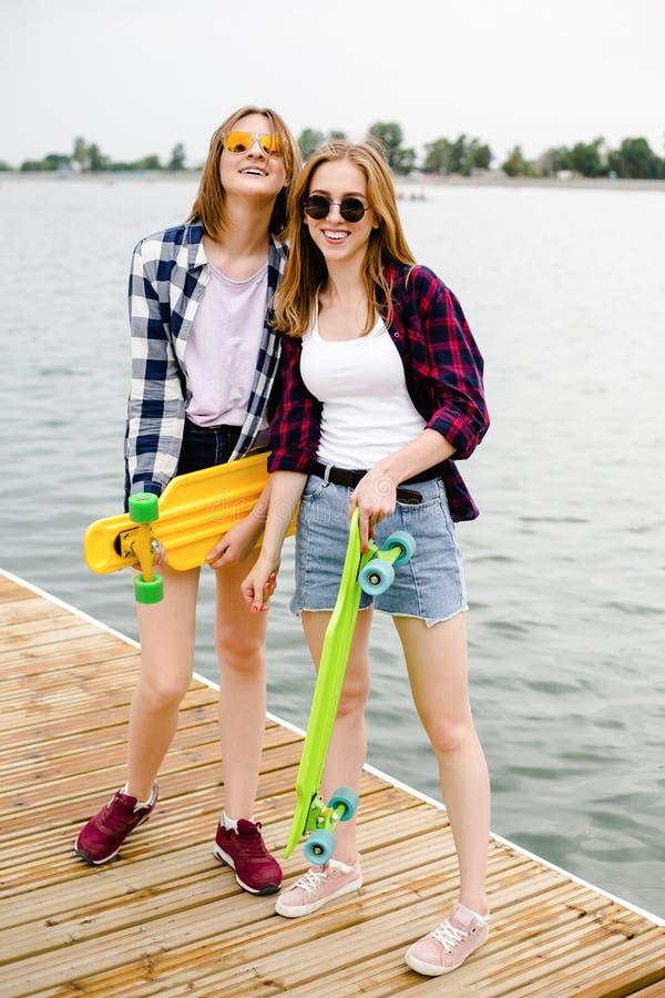 Deux filles heureuses gaies de patineur dans l'équipement de hippie ayant l'amusement sur un pilier en bois pendant des vacances  photo stock