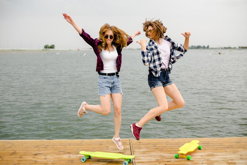 Deux filles heureuses gaies de patineur dans l'équipement de hippie ayant l'amusement sur un pilier en bois pendant des vacances  photographie stock libre de droits