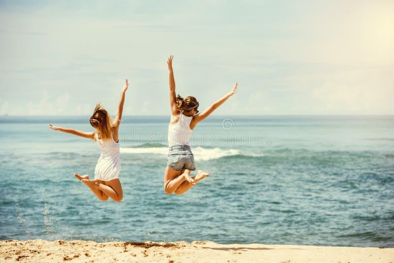 Deux filles heureuses saute à la plage ensoleillée photo stock