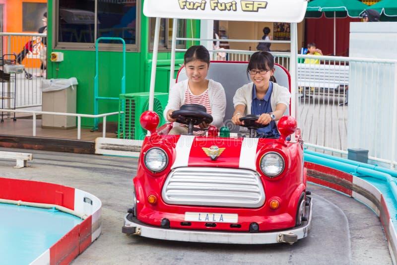 Deux filles japonaises heureuses montant sur une voiture de généraliste de Furi Furi à Tokyo D images libres de droits