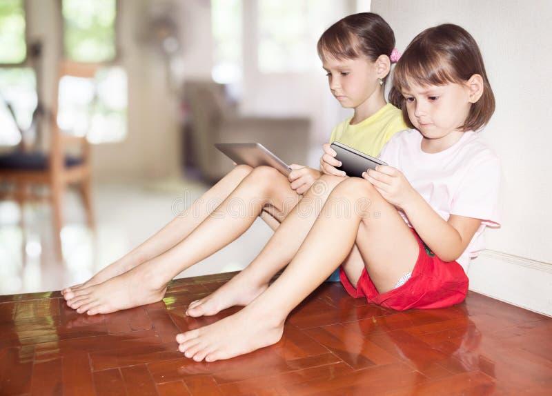 Deux filles jouant au comprimé et au téléphone photos stock
