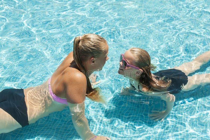 Deux filles jouant dans la piscine image stock