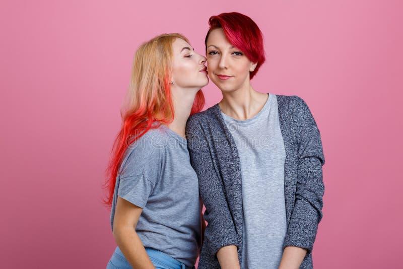 Deux filles lesbiennes, une embrasse des autres sur la joue Sur un fond rose photos libres de droits