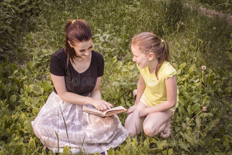 deux filles lisent un livre se reposant sur l'herbe photo libre de droits