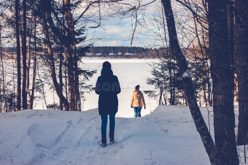Deux filles marchent par la forêt d'hiver au lac photo stock