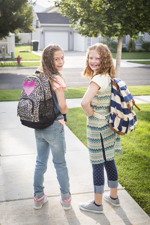 Deux filles mignonnes d'école se dirigeant à l'école photo stock