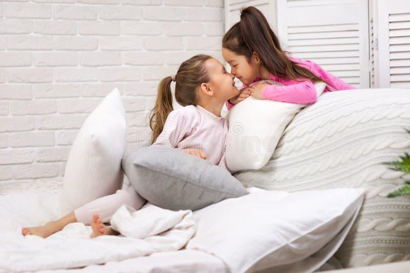Deux filles mignonnes heureuses d'enfants jouant dans la chambre ? coucher photographie stock libre de droits