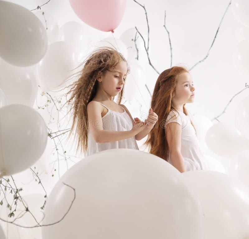 Deux filles mignonnes parmi les ballons photos libres de droits