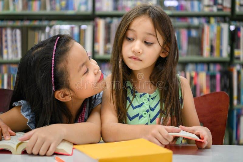 Deux filles mignonnes sont jalouses de l'un l'autre tandis que des livres de lecture dans la bibliothèque tandis qu'enseignement  images stock