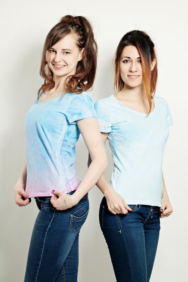 Deux filles mignonnes utilisant le T-shirt Verticale de mode photographie stock