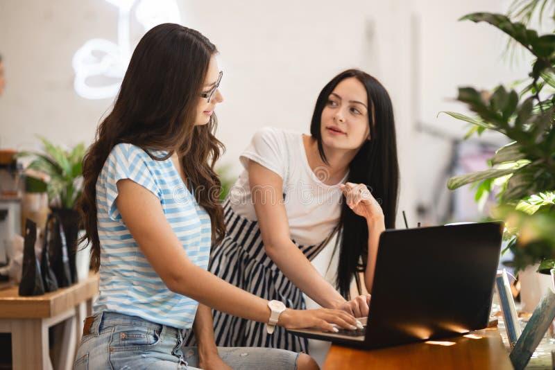 Deux filles minces mignonnes avec de longs cheveux foncés, style occasionnel de port, s'asseyent à la table et regardent attentiv image stock