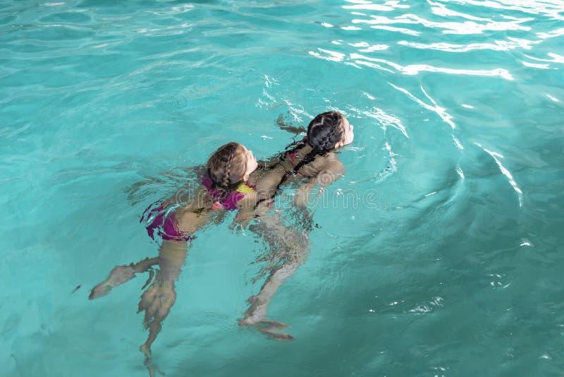 Deux filles nagent dans la piscine Deux soeurs dans la piscine Deux filles heureuses jouent dans la piscine Les belles filles nag images libres de droits