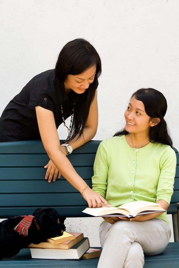 Deux filles ont plaisir à discuter un livre photo stock