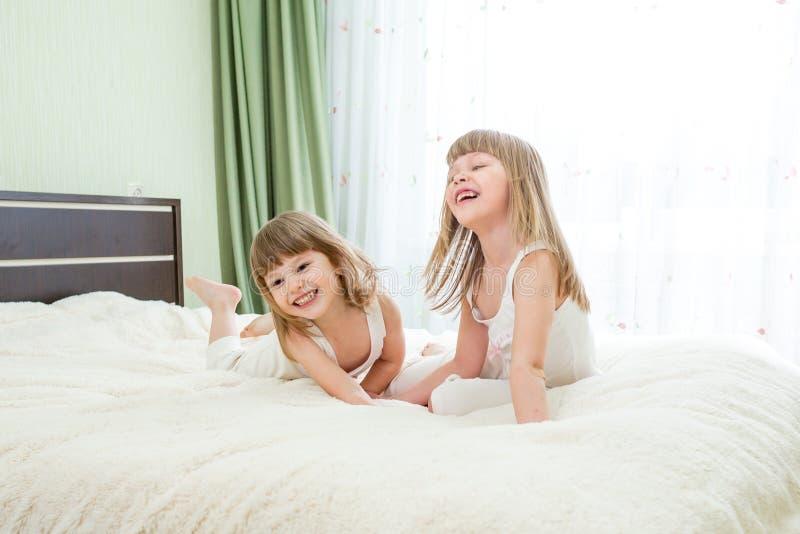 Deux filles ou enfants heureux se trouvant sur le lit photographie stock libre de droits