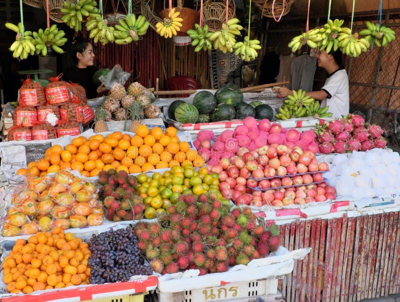 Deux filles près du compteur avec un bon nombre de fruits tropicaux Boîtes avec des raisins, mandarines, photographie stock libre de droits