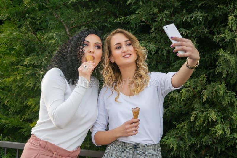 Deux filles prennent des selfies et mangent la crème glacée  image libre de droits