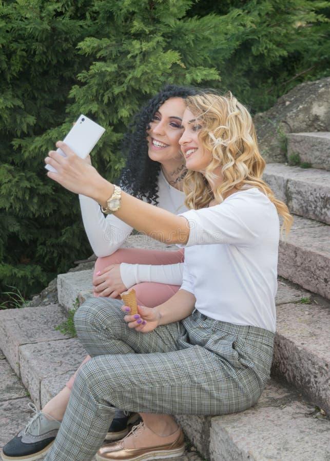 Deux filles prennent des selfies et mangent la crème glacée  images libres de droits