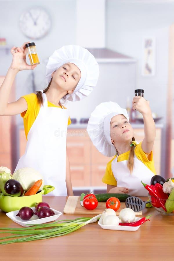 Deux filles regardent étroitement ce qui se situe dans des pots avec des épices photos stock