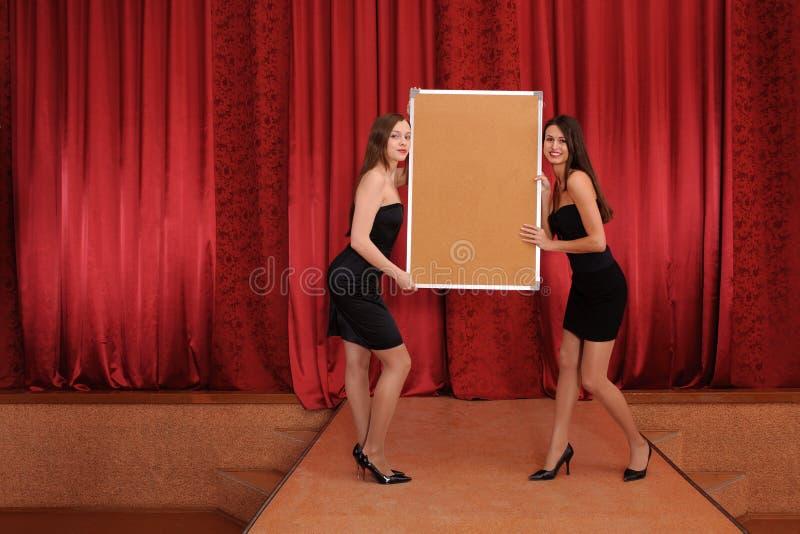 Deux filles retiennent le panneau vide