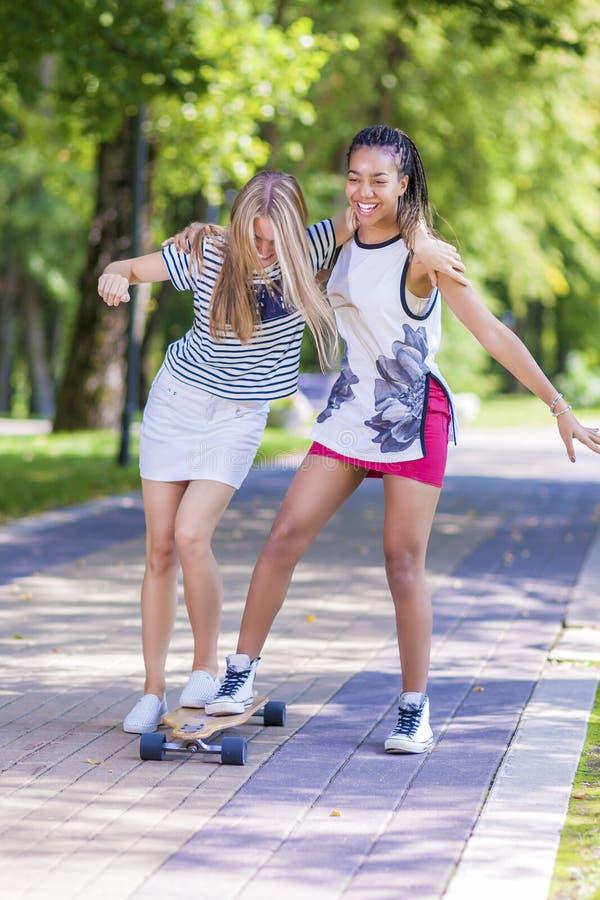 Deux filles riantes heureuses Longboard de patinage d'adolescent ensemble en parc photos stock