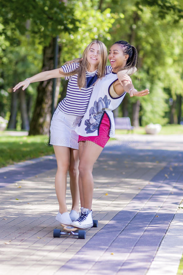 Deux filles riantes heureuses Longboard de patinage d'adolescent ensemble en parc image stock
