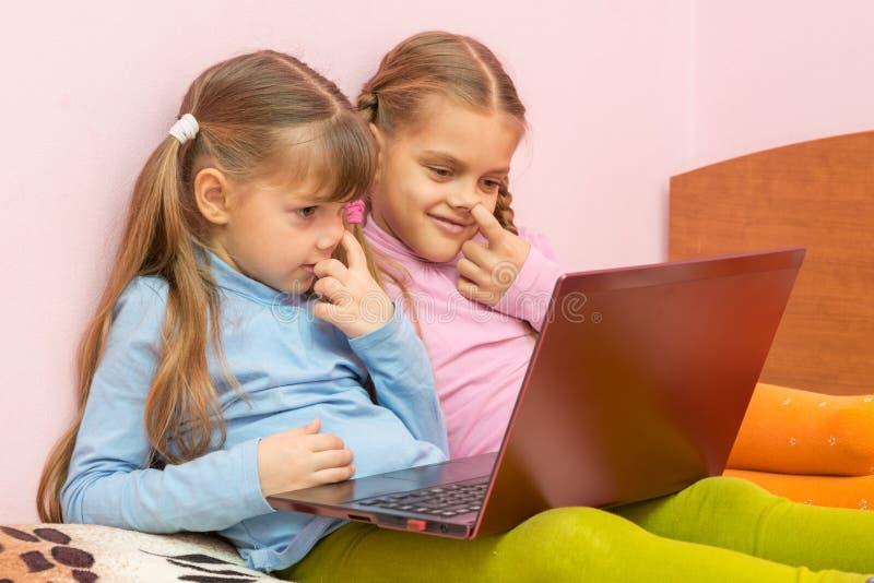 Deux filles sélectionnant son nez et regardant l'écran d'ordinateur portable photo libre de droits