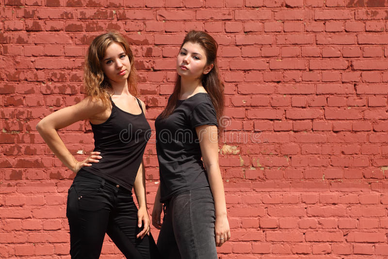Deux filles sérieuses dans les mêmes vêtements noirs photographie stock libre de droits