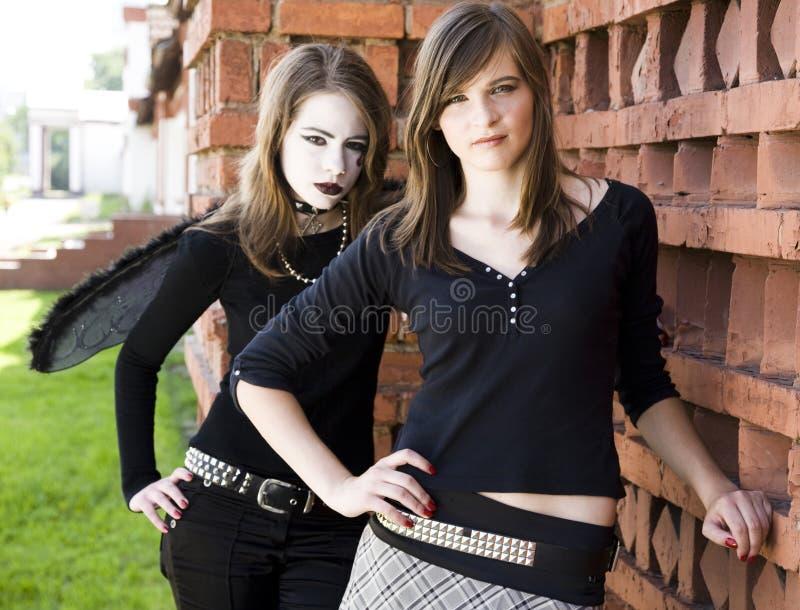 Deux filles s'approchent du mur de briques image libre de droits