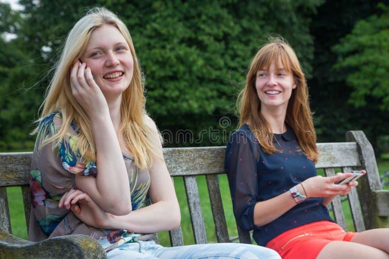 Deux filles s'asseyant sur le banc en parc avec le mobile photo libre de droits